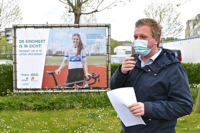 De Izegemse burgemeester Bert Maertens bij een banner met wielrenster Marith Vanhove. Zij is een van de gezichten van de lokale vaccinatiecampagne.
