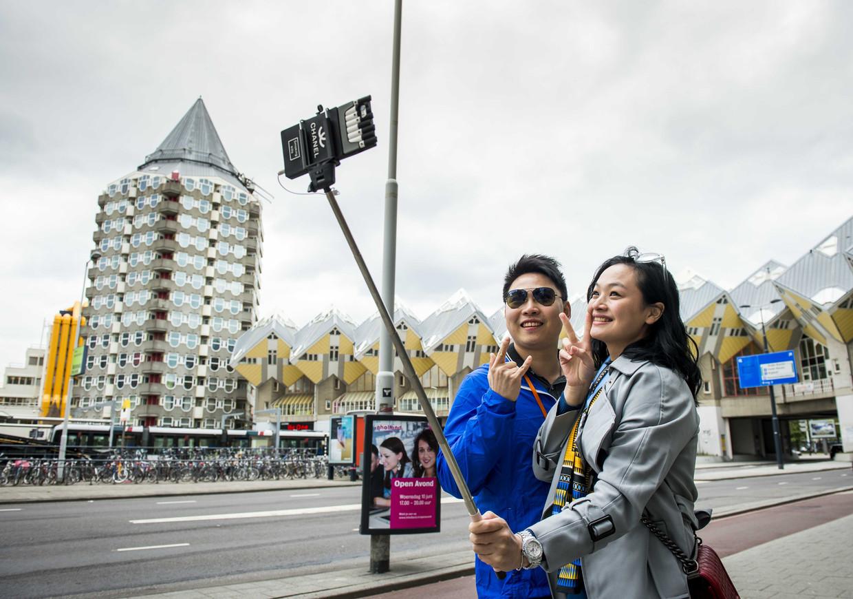 Chinese toeristen maken een selfie bij de kubuswoningen in Rotterdam. Beeld ANP