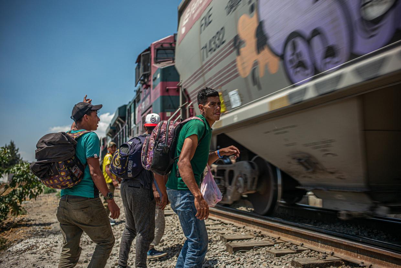 Migranten uit Centraal-Amerika proberen in het Mexicaanse stadje Apizaco op vrachttrein 'Het Beest' te klimmen. Deze poging mislukt, de trein rijdt dit keer te hard. Beeld Alejandro Cegarra