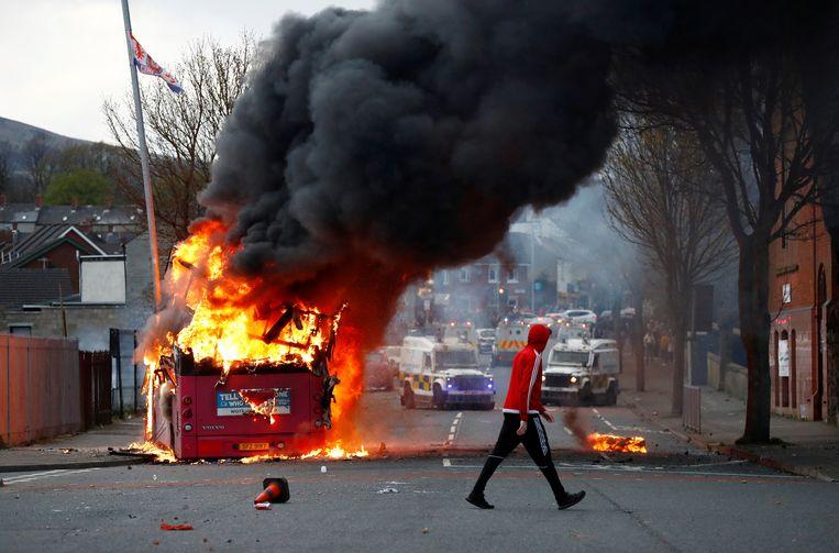 Een brandende dubbeldeksbus in Belfast. Voor de zesde achtereenvolgende nacht waren er rellen in de Noord-Ierse stad. Beeld REUTERS
