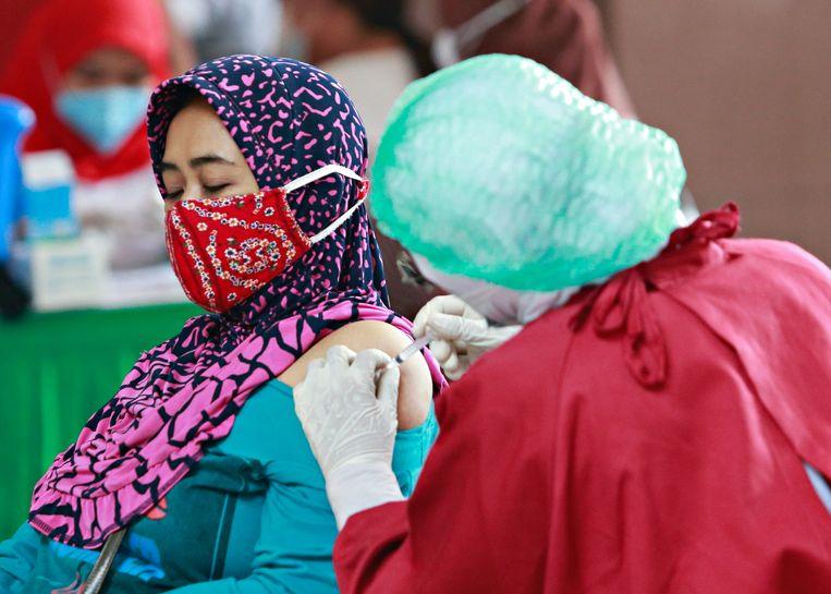 Een vrouw in Jakarta, Indonesië wordt ingeënt. Vaccinweigeraars in deze miljoenenstad riskeren een boete van omgerekend 300 euro.   Beeld Reuters