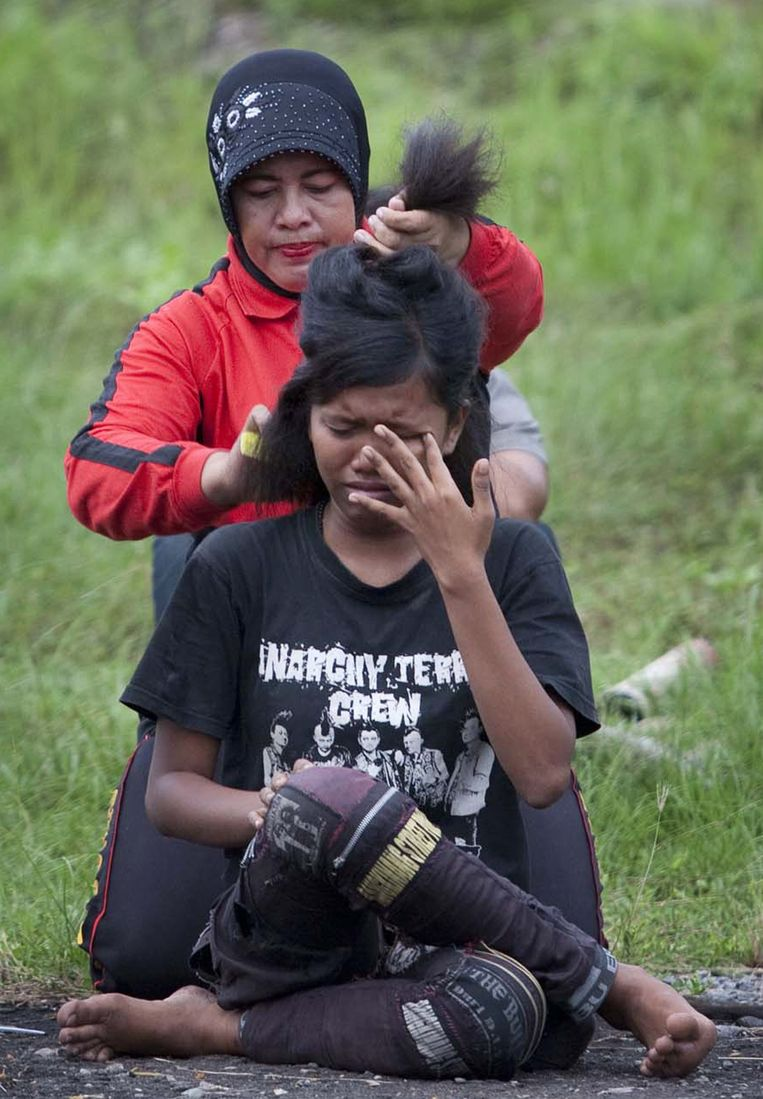 In this photograph taken on December 13, 2011 an Indonesian police woman cuts the hair of a detained punk at a police school in Aceh Besar in Aceh province. Sharia police are