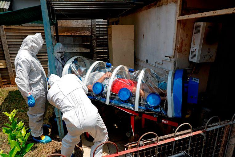 Zorgverleners van een speciale Zuid-Afrikaanse infectie-eenheid voeren een man met coronasymptomen af in een isolatiecabine. Beeld AFP