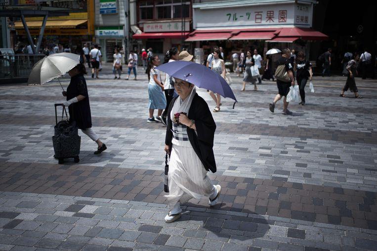 Voetgangers met parasols op straat in Tokyo.  Beeld AFP