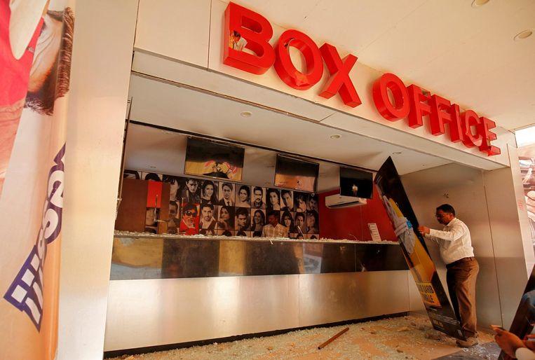 Een manager van een bioscoop neemt de schade op nadat demonstranten zijn bioscoop bestormden. Beeld reuters