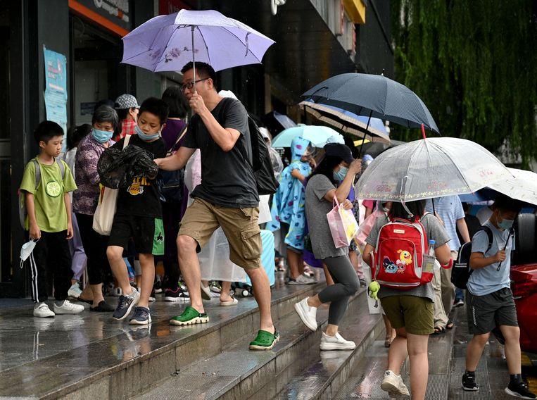 Ouders en leerlingen bij een privéonderneming voor naschoolse bijlessen in Beijing. De overheid heeft dergelijke instellingen onlangs tal van beperkingen opgelegd.  Beeld AFP