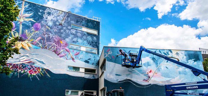 """Het is een flinke klus. De kunstenaar begon vorige week vrijdag en is nog tot vrijdag of zaterdag bezig. ,,Het is pezen want de muur is korreliger dan verwacht. Maar ach, het gaat best rap."""""""