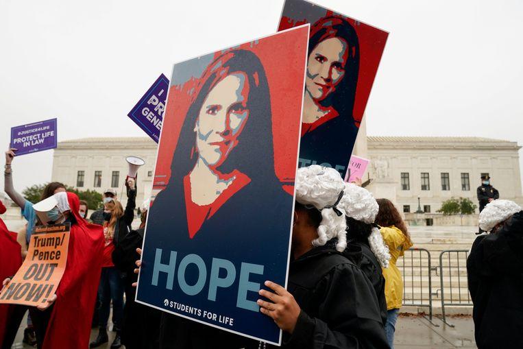Zowel de voor- als tegenstanders van Amy Coney Barrett als nieuwe rechter van het Amerikaans Hooggerechtshof betogen aan de voet van de U.S Supreme Court in Washington. Beeld REUTERS