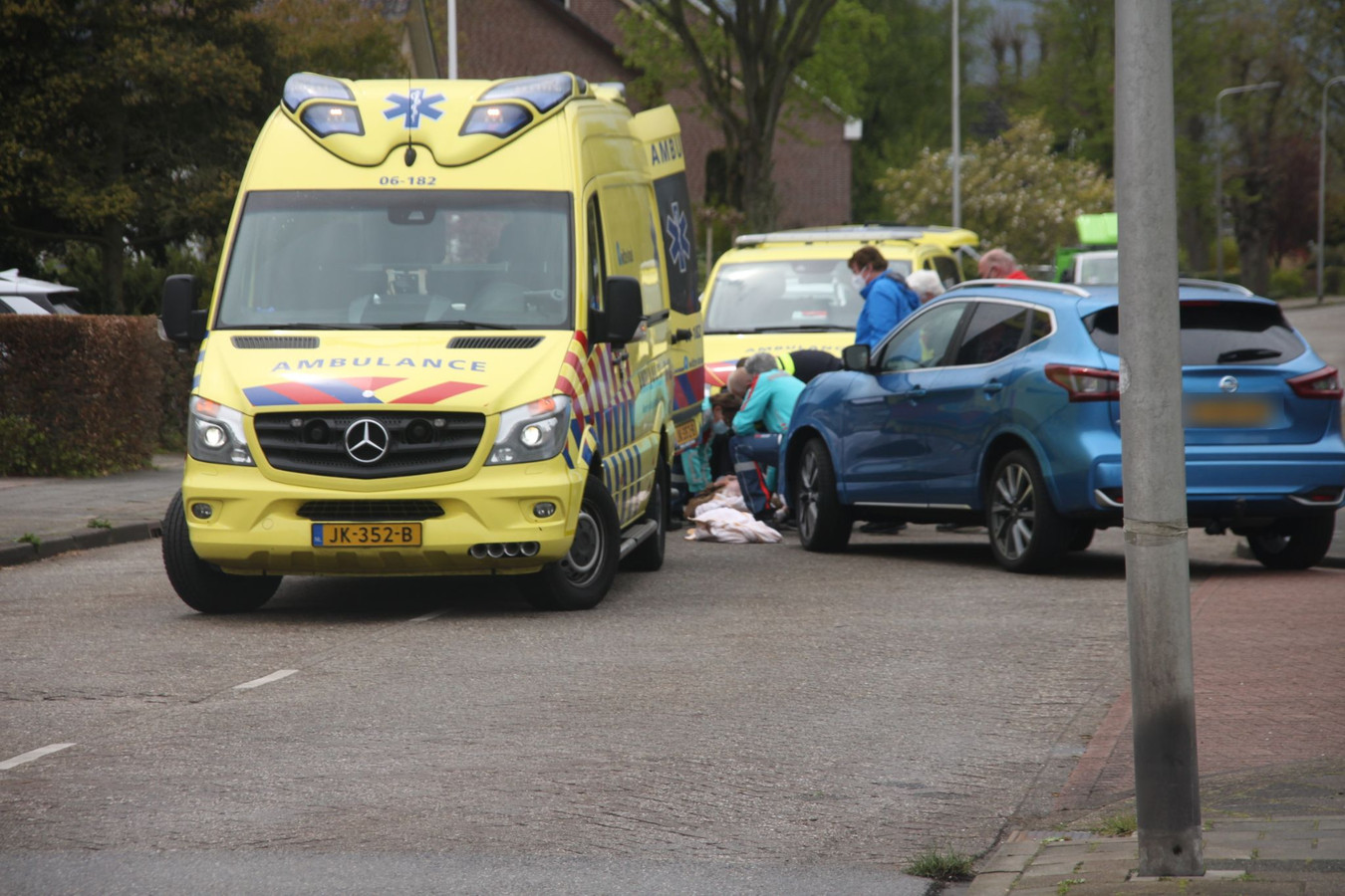 Het ambulancepersoneel buigt zich over het slachtoffer.