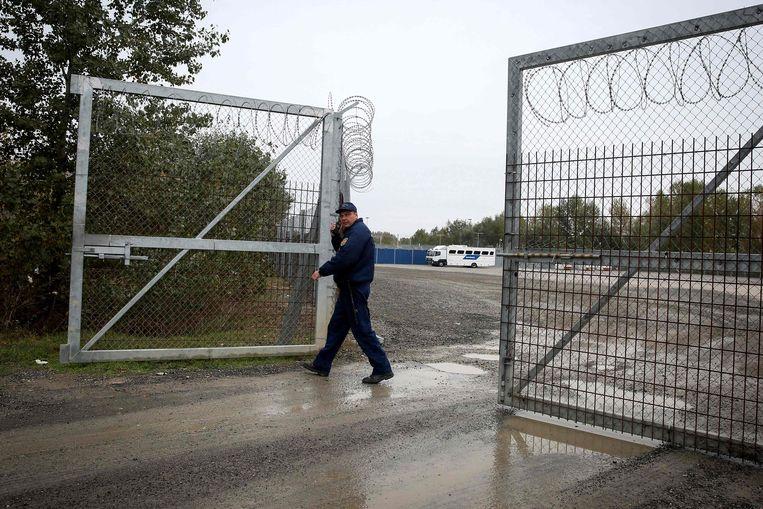 Een Hongaarse politieman sluit een ijzeren hek bij een migrantentransit-centrum nabij Roszke, aan de grens van Servië.  Beeld AFP