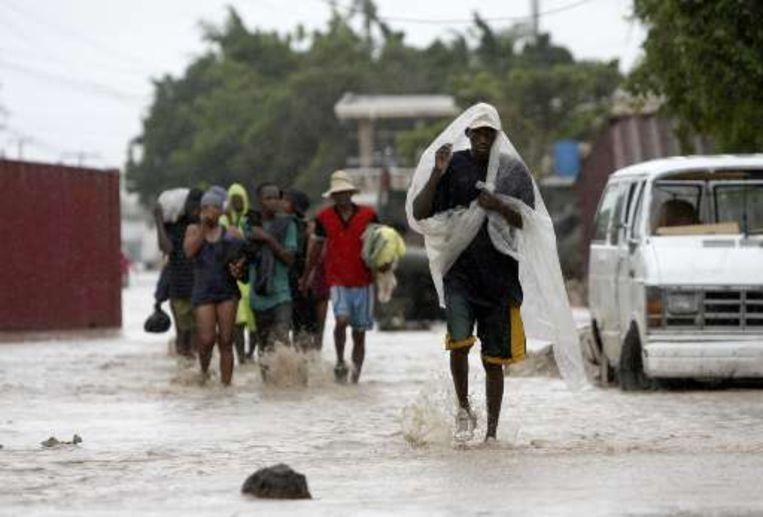 Inwoners van het Haïtiaanse Gonaives waden door een overstroomde straat. Beeld UNKNOWN