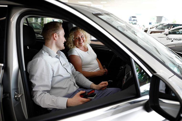 Mirlen Stöffel (rechts) laat zich in haar nieuwe lease-auto de snufjes van het dashboard uitleggen. Beeld Daniel Rosenthal / de Volkskrant