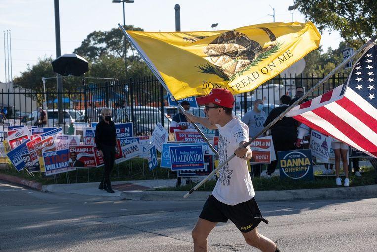 Alejandro Robles (21) loopt wapperend met vlaggen over straat om zijn steun aan Trump te tonen. Beeld Eline van Nes