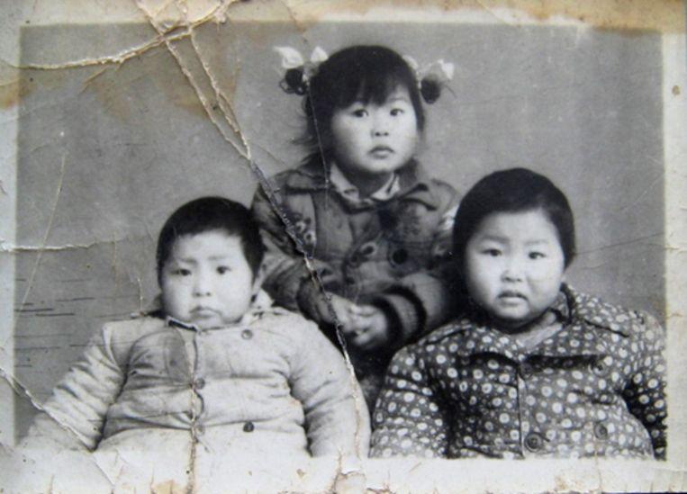 Zhang Hongbing als kind met zijn zus en broer. Beeld Privé-archief