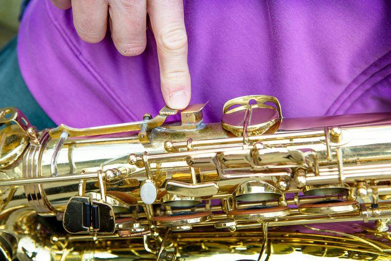 Ties Mellema wijst op de aangepaste klep op zijn saxofoon, waardoor hij na het ongeluk aan zijn hand toch weer kon spelen.  Beeld Pauline Niks