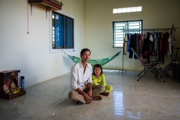Chhim Sarin thuis in Takeo met zijn dochter. Een half jaar geleden verloor hij zijn baan in een textielfabriek. Sindsdien komen hij en zijn vrouw nog maar moeilijk rond. Beeld Antoine Raab