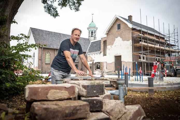 Marco Bergsma voor het parochiehuis en de hervormde kerk in Overdinkel. De aannemer geniet ervan om van een bijzonder pand weer iets moois te maken.