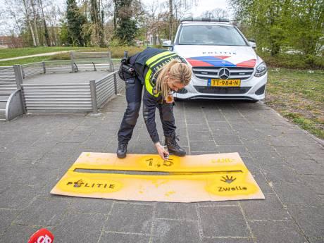 Politie Zwolle pakt de spuitbus en kalkt de boodschap op het asfalt: 1,5 meter afstand graag!