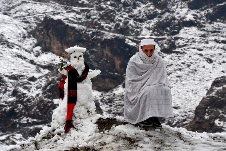 Een man poseert naast een sneeuwpop na het vallen van de eerste sneeuw in Landi Kotal in het noorden van Pakistan.  Beeld AFP