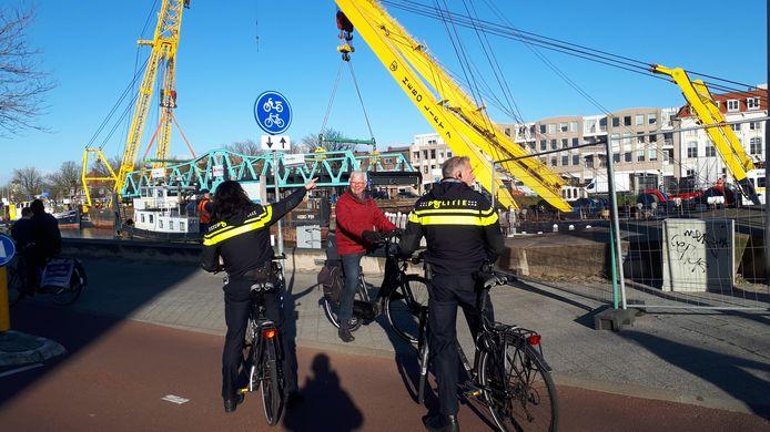 Politie-agenten vragen voorbijgangers vriendelijk of ze willen doorrijden. Kijken naar het terugplaatsen van de Stationsbrug is niet de bedoeling.