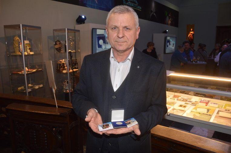 Yvan Roelandt, voorzitter van de VVV-Ninove vzw, met de souvenirpenning (midden) en de magneten.