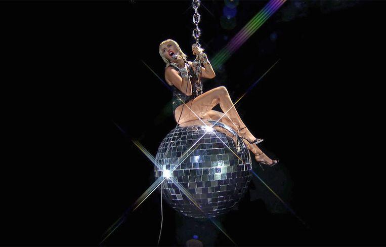 'Van 'Wrecking Ball' herinnert niemand zich de pijn die in dat nummer zit, maar iedereen weet wél dat ik naakt op die bal zat.' (Foto: Miley Cyrus met een vette knipoog naar de clip uit 2013.) Beeld AFP