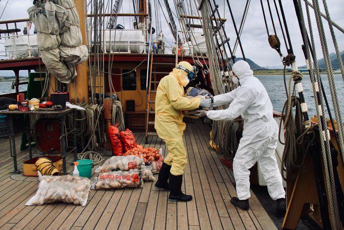 Voedsel wordt met beschermende pakken aan oord gebracht van de Bark Europa. Uit voorzorg om corona buiten het schip te houden.
