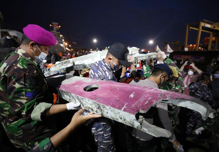 Soldaten en andere hulpverleners vervoeren brokstukken van de Boeing die zaterdag crashte in de Javazee. Beeld AP