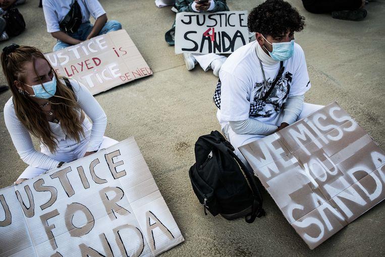 Vrienden van Sanda zitten op de grond terwijl ze hun vriend herdenken.  Beeld Bas Bogaerts