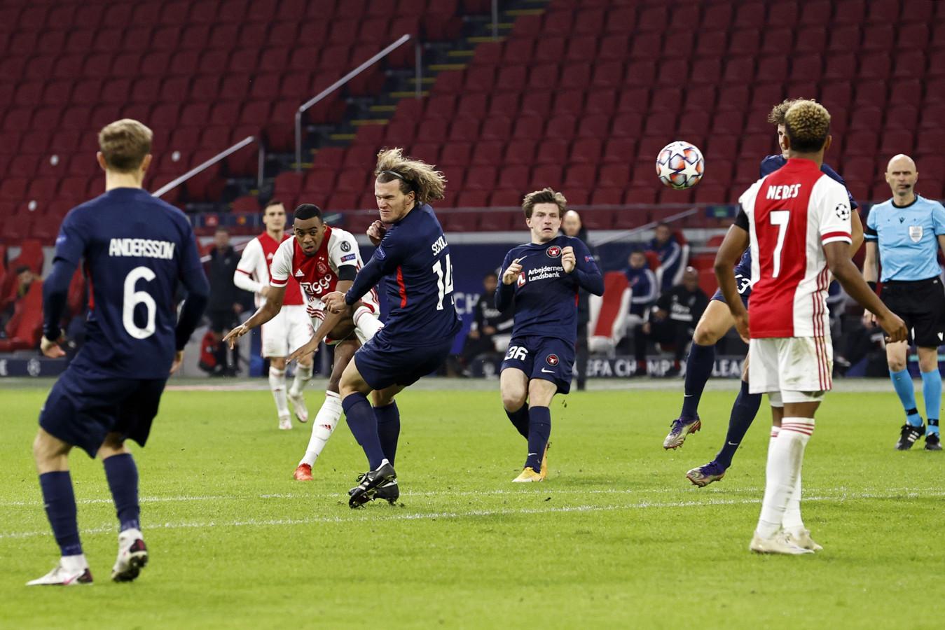 Ryan Gravenberch haalt de trekker over tegen FC Midtjylland. Rechts scheidsrechter Sergej Karasev.