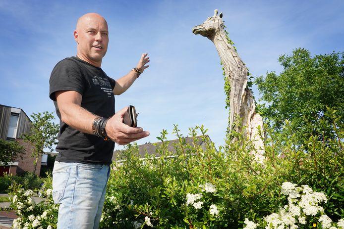 Jan-Carel Koster bij het door hem gemaakte houten beeld speeltuin bij de Hogenhof. De giraf is het enige dier dat nog is overgebleven van het kunstwerk.