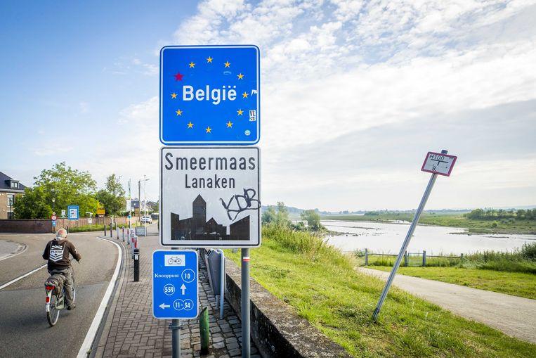 Een fietser passeert de grens tussen België en Nederland. Reizigers die vanaf 8 augustus terugkeren naar Nederland, kunnen worden gecontroleerd of ze coronavrij dan wel beschermd zijn tegen het virus. Beeld ANP