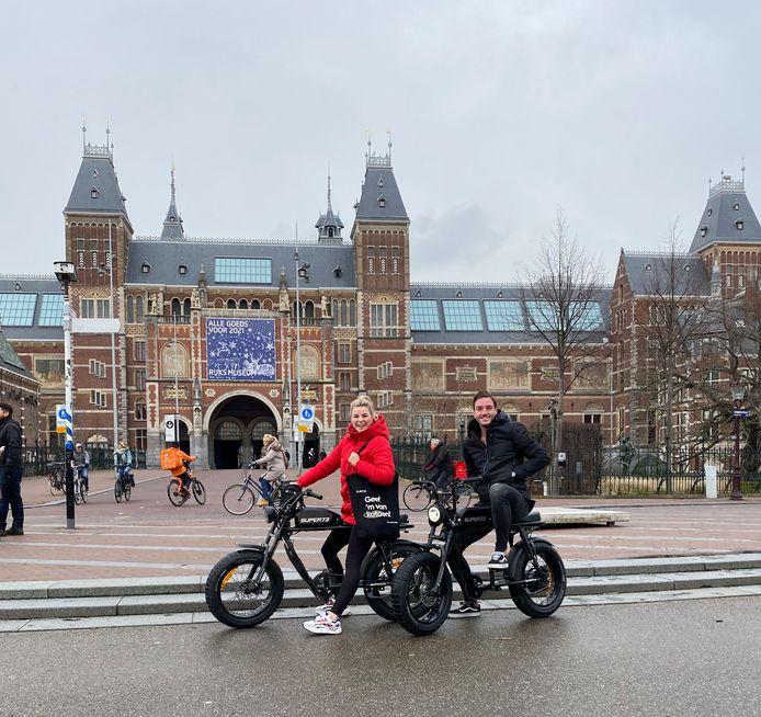Yara Heisterkamp en Stijn Bruns maken op hun hippe e-bikes een rondje langs klanten in Amsterdam.