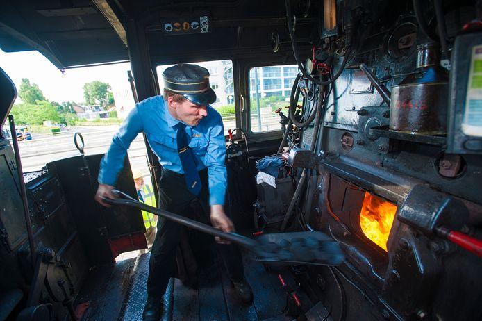 Op een hete dag kolen scheppen in een van de locs van de Veluwsche Stoomtrein Maatschappij tussen Dieren en Apeldoorn.