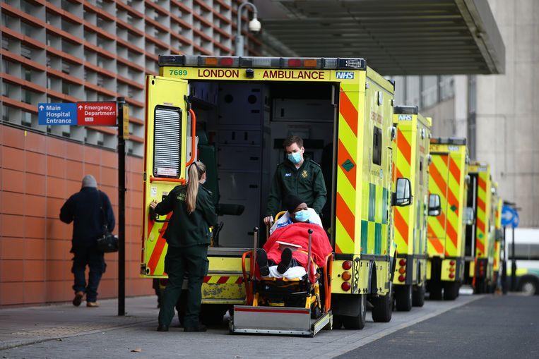 Een lange rij van ambulances voor The Royal London Hospital in Londen. De coronapatiënten stromen toe in ziekenhuizen in heel Groot-Brittannië. Beeld Getty Images