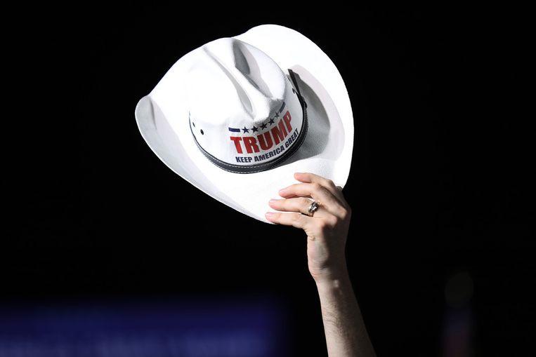 Een cowboyhoed wordt opgehouden terwijl mensen wachten op de komst van de Amerikaanse president Donald Trump voor zijn campagne-evenement in Opa Locka, Florida. Beeld Getty Images
