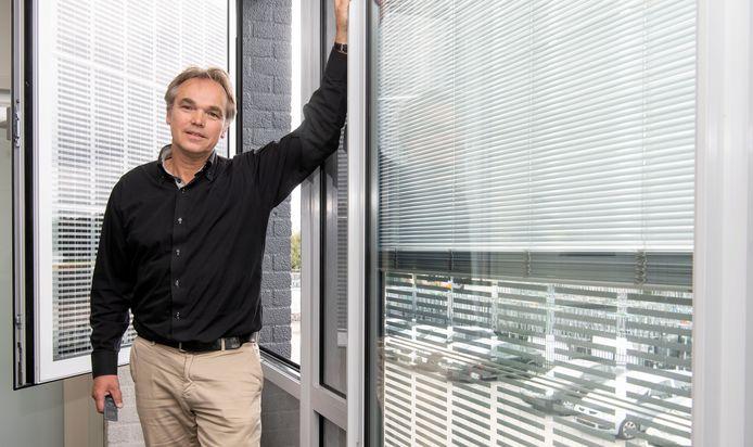 Innovatiemanager Marcel Ribberink van Pilkington bij het revolutionaire glas, dat energie opwekt en warmte afgeeft.