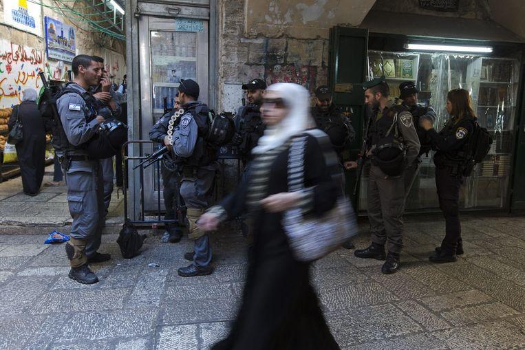 Een Palestijnse vrouw passeert Israëlische politie op weg naar de al-Aqsa-moskee. Beeld epa