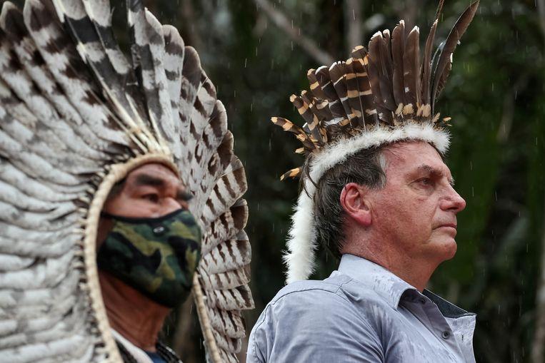 De Braziliaanse president Jair Bolsonaro, rechts, luistert naar het volkslied tijdens een bezoek aan Yanomami, een reservaat in het Amazonegebied, aan de grens met Venezuela. Het is onrustig in het gebied, omdat grondstofdelvers er voet aan de grond proberen te krijgen.  Beeld via REUTERS