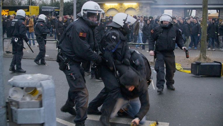 Een fan van Dortmund wordt bij de lurven gegrepen door de politie. Beeld AFP