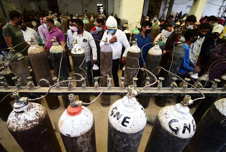 Indiërs hervullen zuurstofflessen voor coronapatiënten in de stad Allahabad. Op veel plekken in India is een tekort aan zuurstof. Beeld AFP