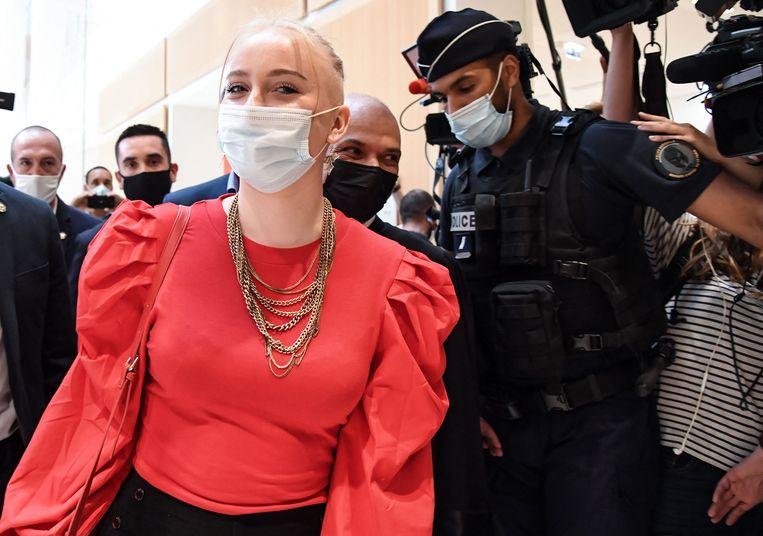 De 18-jarige Mila loopt naar de rechtszaal, waar dertien mensen terechtstaan voor online intimidatie aan haar adres.    Beeld AFP