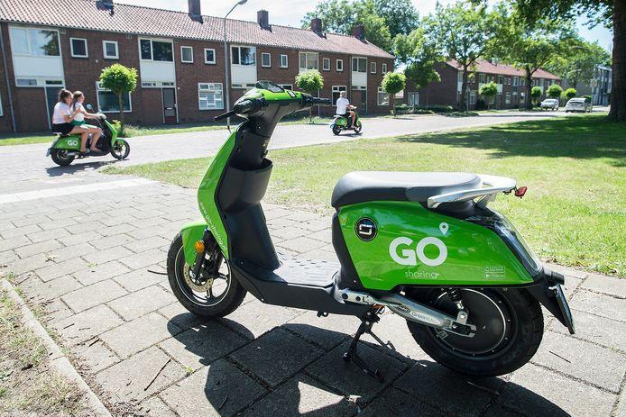 Een scooter van Go Sharing op de stoep aan de Lage Kant in de wijk Brabantpark in Breda. Op de achtergrond zijn er twee in gebruik.