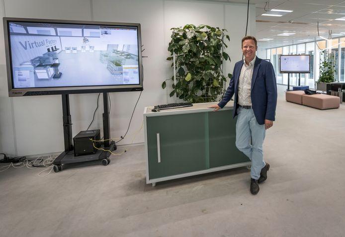 Wim Renders in het bezoekerscentrum met op het beeldscherm een virtuele fabriek.