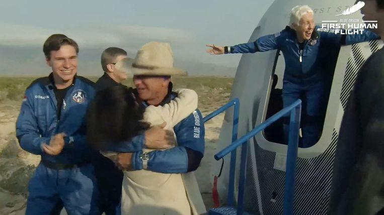 Jeff Bezos (midden), Wally Funk (rechts) en Oliver Daemen (links) stappen uit de capsule na de landing. Beeld AFP