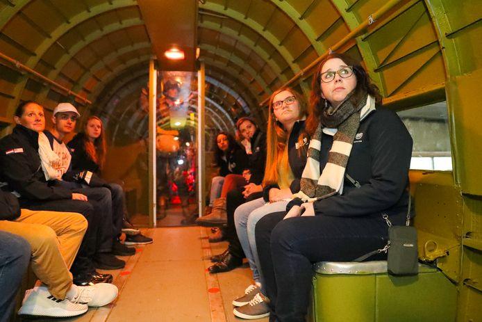 Amerikaanse scholieren en docenten zitten in de romp van de DC 3 Dakota van Bevrijdende Vleugels.  Tweede van links met witte pet is Tommy Williams.