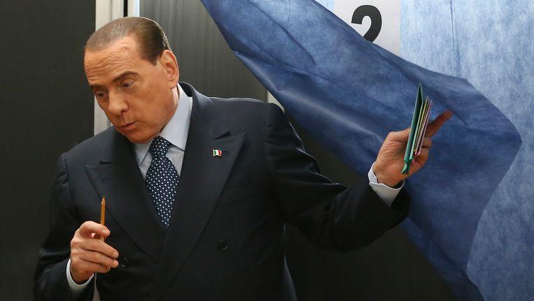 Silvio Berlusconi verlaat zijn stemhokje Beeld AP