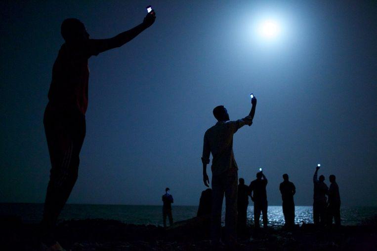 World Press Photo of the Year 2013<br /><br />Vluchtelingen in Djibouti houden hun telefoons in de lucht om te proberen een signaal uit Somalie op te vangen, zodat ze goedkoop naar hun familie kunnen bellen. Beeld John Stanmeyer