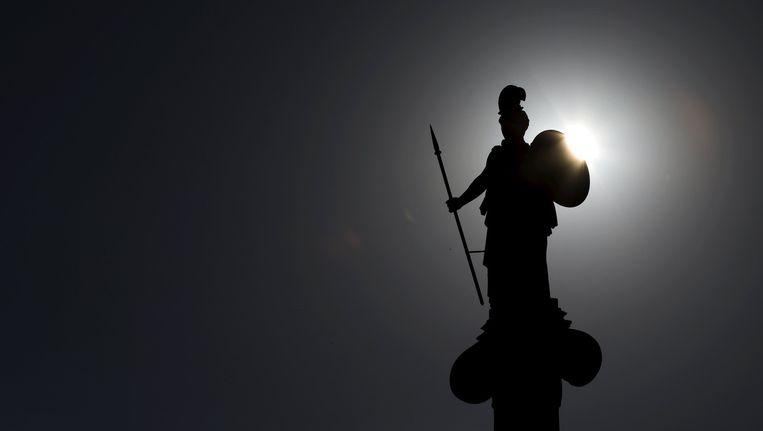 De zon komt op achter een standbeeld van de Griekse godin Pallas Athena, in de Griekse hoofdstad Athene. Beeld reuters
