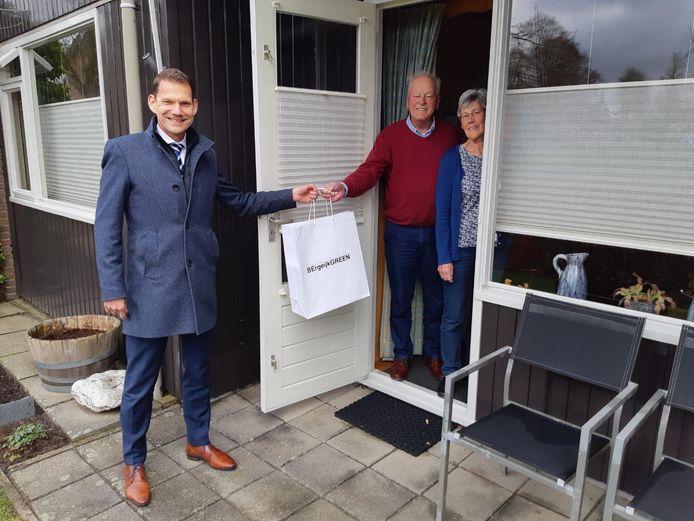 Gemeentesecretaris Hans Loos reikt een presentje uit aan het paar Intven-Hakkens in Riethoven.